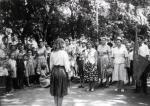 Сдаются рапорта перед отправкой детей в пионерский лагерь. Парк возле ТЮЗа. Начальник лагеря Агния Петровна Агапова.